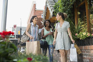 Women friends talking and carrying shopping bags on urban sidewalk - HEROF14250