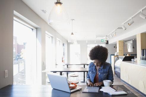 Woman working at digital tablet in cafe - HEROF14253