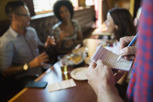 Waiter taking order at table in bar - HEROF14256