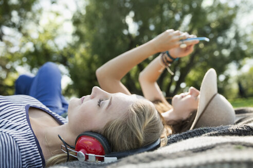 Women friends relaxing listening to music and using cell phone on blanket in park - HEROF14262