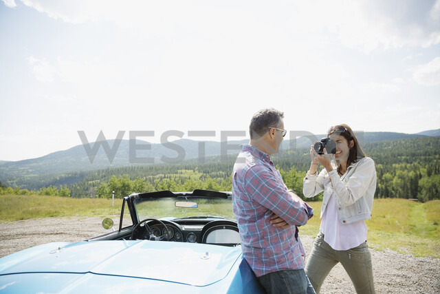 Wife photographing husband at convertible at rural overlook - HEROF14265