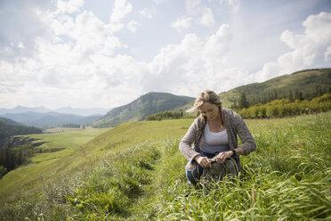 Woman hiking crouching in remote sunny rural field - HEROF14268