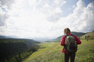 Woman with backpack hiking in remote sunny rural field - HEROF14271
