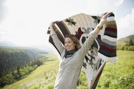 Woman holding picnic blanket in sunny remote rural field - HEROF14274
