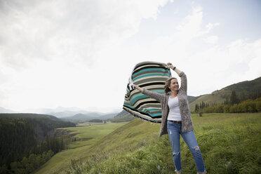 Woman holding blanket in wind in remote rural field - HEROF14277