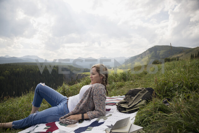 Woman relaxing on blanket in remote rural field - HEROF14280 - Hero Images/Westend61