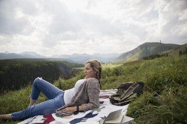 Woman relaxing on blanket in remote rural field - HEROF14280