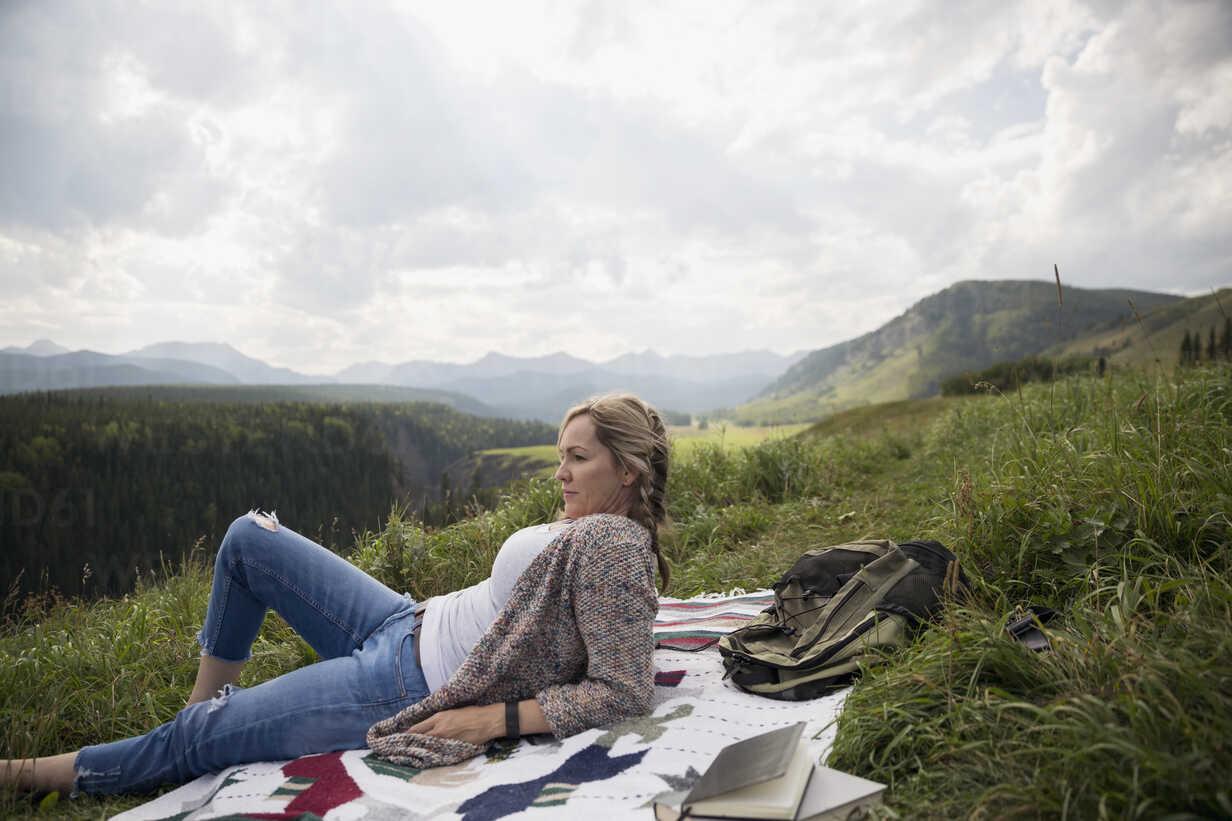 Woman relaxing on blanket in remote rural field - HEROF14280 - Hero Images/Westend61