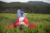 Woman relaxing laying in grass in remote rural field - HEROF14286