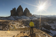 Italy, Tre Cime di Lavaredo, man hiking and standing in front of the majestic three peaks - WPEF01331