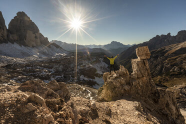 Italy, Tre Cime di Lavaredo, man hiking and looking at the valley with peaks and sun over the horizon - WPEF01334