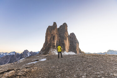 Italy, Tre Cime di Lavaredo, man hiking and standing in front of the majestic three peaks - WPEF01337