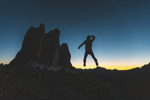 Italy, Tre Cime di Lavaredo, silhouette of a man jumping at the three peaks at dusk - WPEF01340