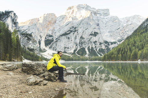 Italy, Braies Lake, man sitting on a rock at the lakeside with mountains and forest in background - WPEF01343