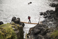 Female backpacker crossing fallen log between cliffs overlooking ocean - HEROF14310
