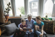 Grandmother and granddaughters using digital tablet on sofa - HEROF14322