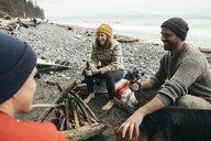 Friends enjoying weekend surfing getaway, drinking beer at campfire on rugged beach - HEROF14379