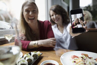 Portrait playful women friends showing selfie photo on camera phone at restaurant - HEROF14451