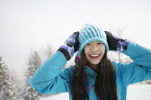 Portrait smiling girl playing in snow - HEROF14487