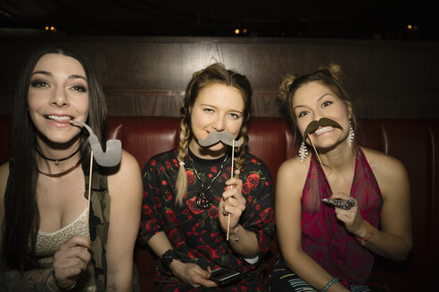 Portrait playful, fun female millennials with mustache and pipe props in nightclub - HEROF14532