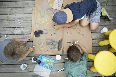 Overhead view brothers painting lemonade stand in back yard - HEROF14562