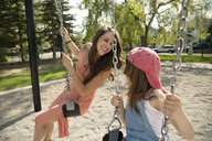 Playful mother and daughter on swings at sunny playground - HEROF14571