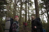 Smiling couple backpacking in woods - HEROF14583