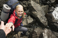 Smiling active senior woman backpacking, reaching for helping hand on rocks - HEROF14586