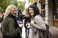 Portrait smiling, confident women friends with coffee walking on city sidewalk - HEROF14595