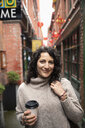 Portrait smiling, confident woman with coffee in urban alley - HEROF14598