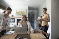 Teenage daughters surprising mother working at laptop with cake - HEROF14679