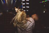 Female millennial dancing, enjoying music concert in nightclub - HEROF14781