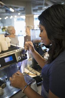 Female barista working at espresso machine in cafe - HEROF14793