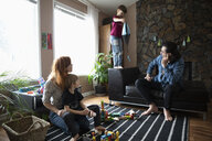 Family playing with parachute and toys in living room - HEROF14796