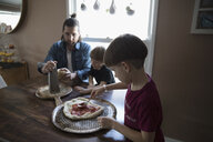 Father and sons making homemade pizza at dining table - HEROF14802