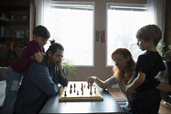 Family playing chess at living room coffee table - HEROF14814