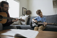 Father teaching son how to play guitar in living room - HEROF14820