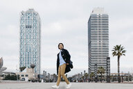 Spain, Barcelona, man walking in the city with two skyscrapers in the background - JRFF02496