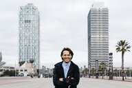 Spain, Barcelona, portrait of laughing man in the city with two skyscrapers in the background - JRFF02499