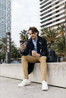 Spain, Barcelona, man sitting in the city with takeaway coffee and cell phone - JRFF02502