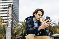 Spain, Barcelona, serious man sitting in the city with takeaway coffee and cell phone - JRFF02505