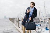 Spain, Barcelona, happy man using cell phone at the harbor - JRFF02514