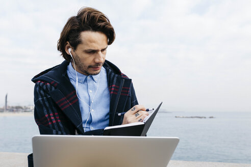 Spain, Barcelona, man sitting at the sea working with laptop and notebook - JRFF02520