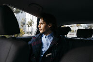 Man sitting on back seat of a car looking out of window - JRFF02526