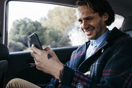 Smiling man sitting on back seat of a car using cell phone - JRFF02529