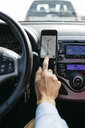 Close-up of man with tattooed hand driving car using cell phone as navigation system - JRFF02538