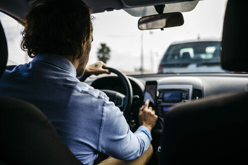 Businessman driving car using cell phone as navigation system - JRFF02541
