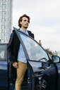 Spain, Barcelona, man getting out of the car with cell phone in his hand - JRFF02547