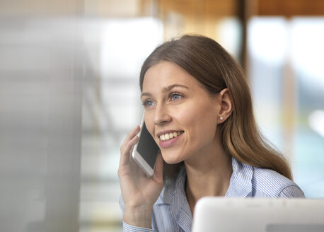 Portait of smiling businesswoman on cell phone in office - ABRF00265