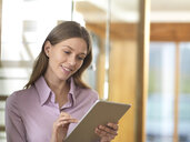 Smiling businesswoman using tablet in office - ABRF00271